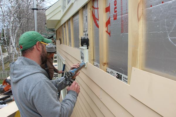 Fenton and Cunningham install the factory primed and first coated vertical grain red cedar clapboards. Field cuts are end-primed, then then bedded in polyurethane sealant where they contact trim elements.