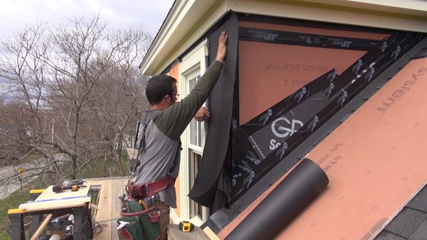 Pollard applies asphalt felt paper over the ZIP sheathing, sliding the top edge of the paper up underneath the unstapled lower edge of a strip of paper already applied to the eave under the trim board. To his left, Pollard tucks the paper under Mortairvent rainscreen fabric already installed under the window trim.