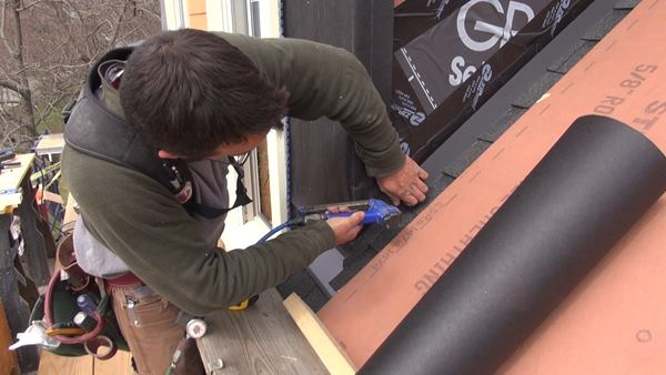 Pollard fastens the bottom edge of the asphalt felt paper over the previously applied self-adhering bituminous membrane flashing that covers the top edge of the aluminum step flashing.