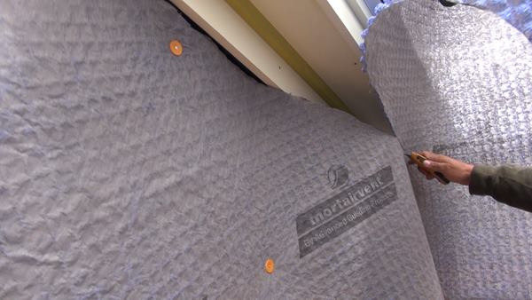 Pollard slices the Mortairvent fabric to fit with a utility knife. Thompson Johnson likes Mortairvent because it lies flat on the wall and is manufactured by a local Maine company (Advanced Building Products, Inc., of Springvale, Maine).
