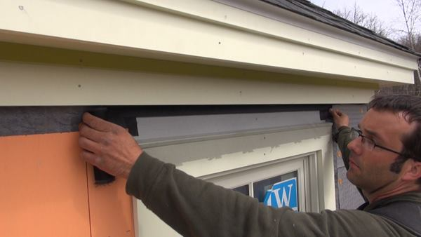 Insect screen is installed over the window cap flashing to allow for a gap between the flashing and siding for airflow and drainage.