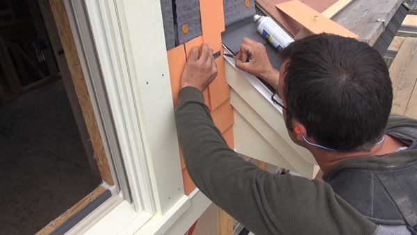 Pollard scribes a wood shingle to fit the profile of the roof trim and metal drip edge. The shingles are factory-dipped with a three-coat finish (one primer coat and two topcoats).