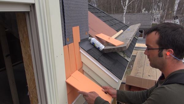 Pollard compares shingle widths to the existing shingle gap as he selects pieces to fill out the course.
