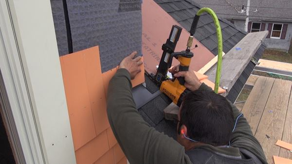 Pollard tacks up pieces of the thin ends of shingles for triple coverage above the roof.