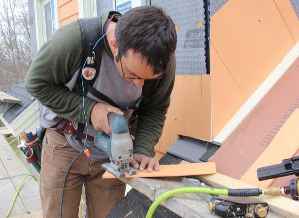 Pollard uses a jigsaw to cut a matching roof angle onto a shingle.