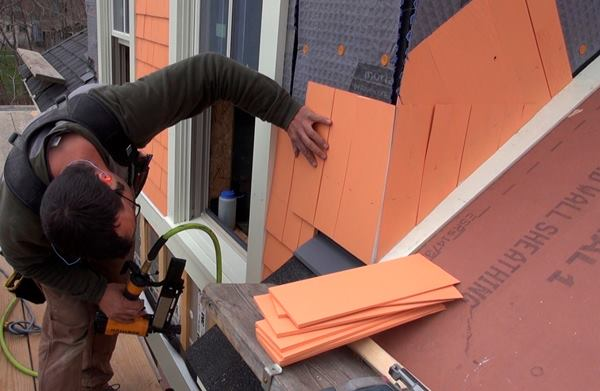 Pollard sets the first full course of shingles above the roof line, leaving a one-inch gap above the heavy-duty metal flashing.