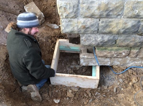 Martignetti sets a wooden footing form under the foundation. The plan is to dig and form up footings in short sections, pour a section of concrete footing and let it set, then excavate and underpin the next short section, and so on.