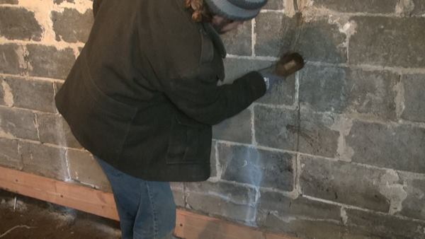 The inside of the block wall is being re-pointed at joints, and and cracks in the block are being ground out to ½-Inch depth and grouted with mortar. Here, mason Joe Martignetti wets the crack with a brush before applying grout
