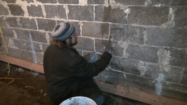 Martignetti works grout into the crack. The entire face of the block foundation will later receive a reinforcing parge of modified cement.