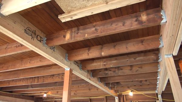 The first floor ceiling (second floor frame) of the old house was originally framed with sawn 2x8 boards more than 26 feet long, spanning the entire downstairs of the house. The floor joists had sagged four inches in the middle of the span. Thompson Johnson cut the joists and two mid-span locations and reframed the floor with two long beams built up with doubled 1.75-inch by 10-inch LVLs, and supported by Douglas Fir posts.