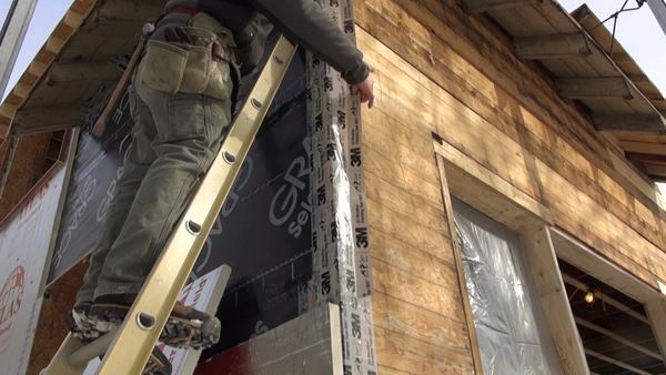 A worker applies 3m 8067 tape to an Ice and Water Shield edge during winter work on the exterior wall build-out.