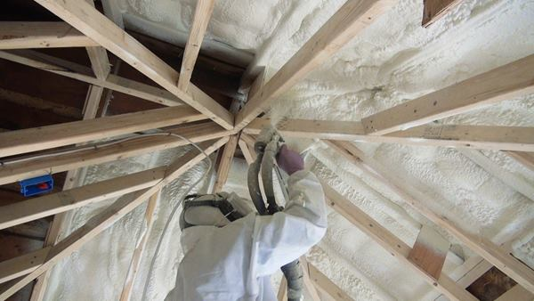 "A technician with Portland, Maine-based I&S Insulation, ""aka Itchy and Scratchy"" ( www.iandsinsulation.com ) applies high-density polyiso spray foam insulation to the underside of the home's existing roof sheathing."