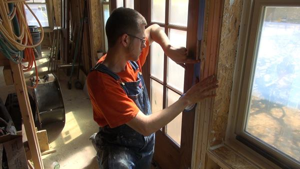 A Thompson and Johnson crew member seals French doors with masking tape as the crew prepares for the blower door test.