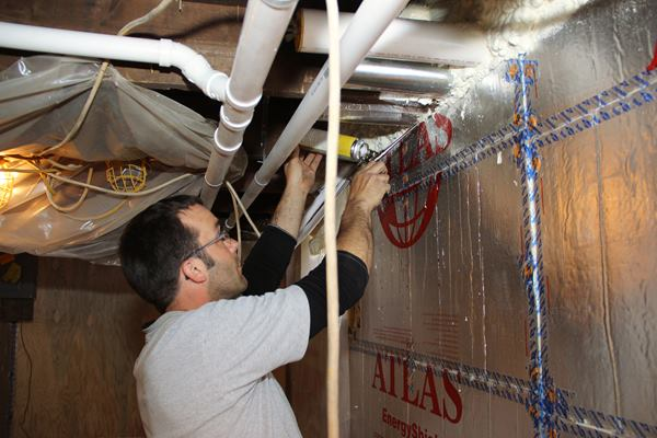 Mark Pollard insulates and seals the gap at the top of the basement wall with a can of gun foam.