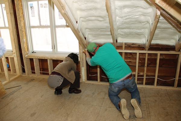 Rachel Conly and Shane Fenton locate and seal small air leaks during blower door testing.