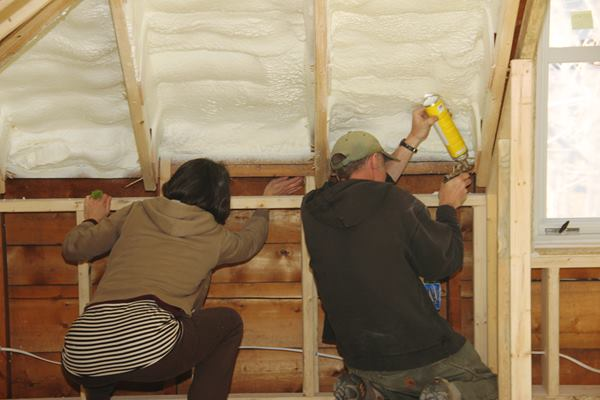 Rachel Conly and Ed Muennich find and seal air leaks.