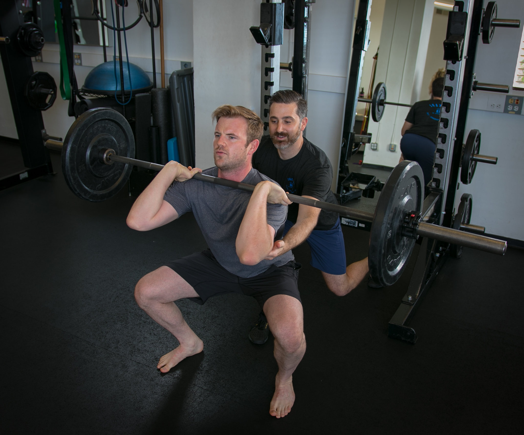 Jake Tipane , coaching his client on proper squat form.