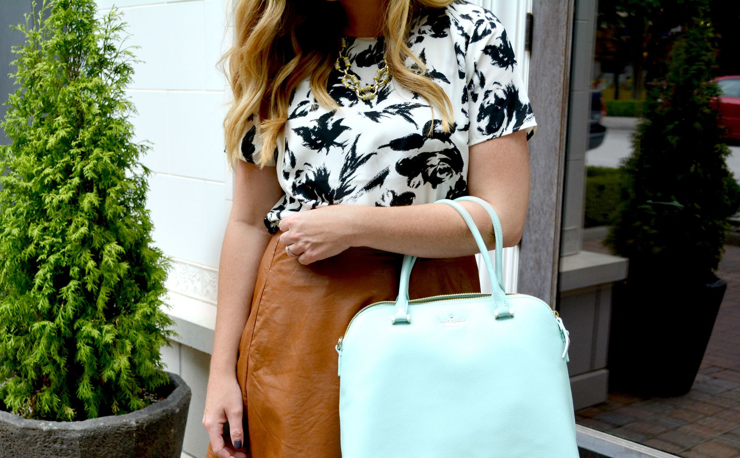 Black and white printed top with brown leather skirt mint Kate Spade bag and gold sandals on Sophisticaited.com
