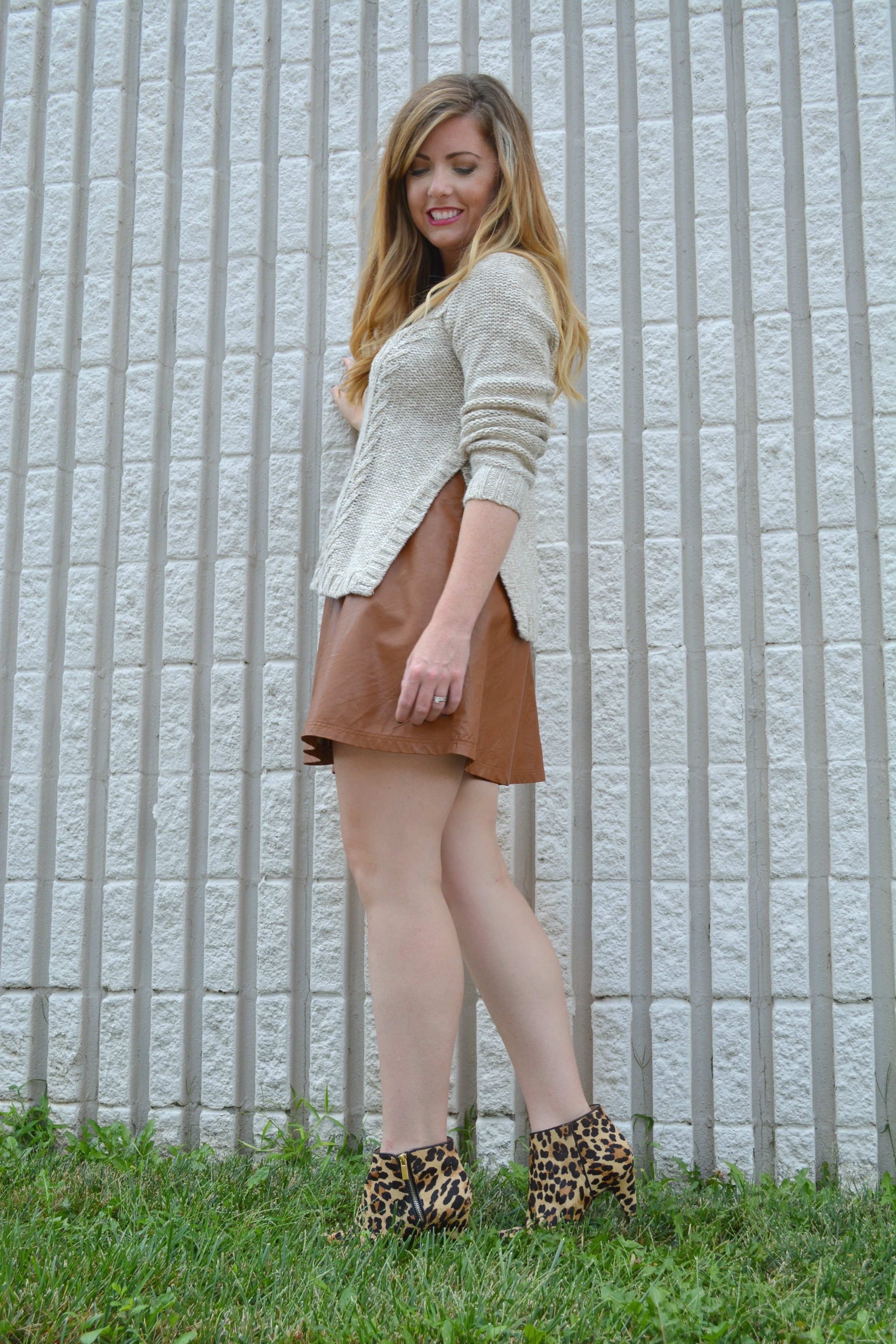Cream sweater worn with tan leather skirt and leopard booties on Sophisticaited