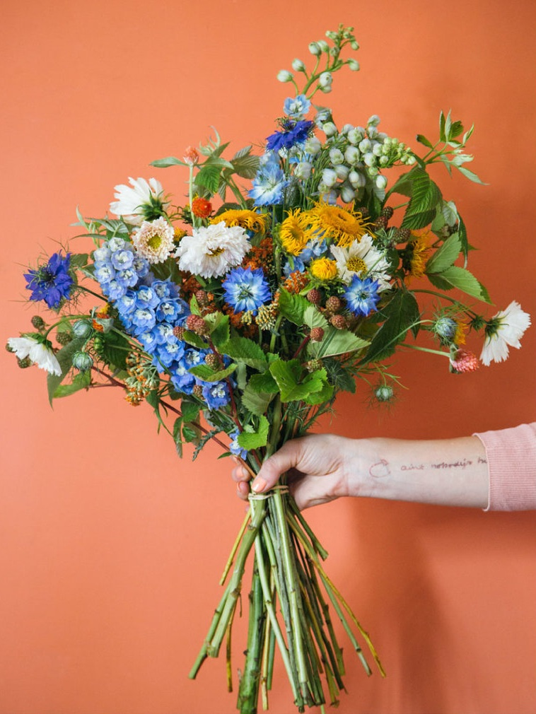 odd flowers hand holding bouquet with flower arrangement