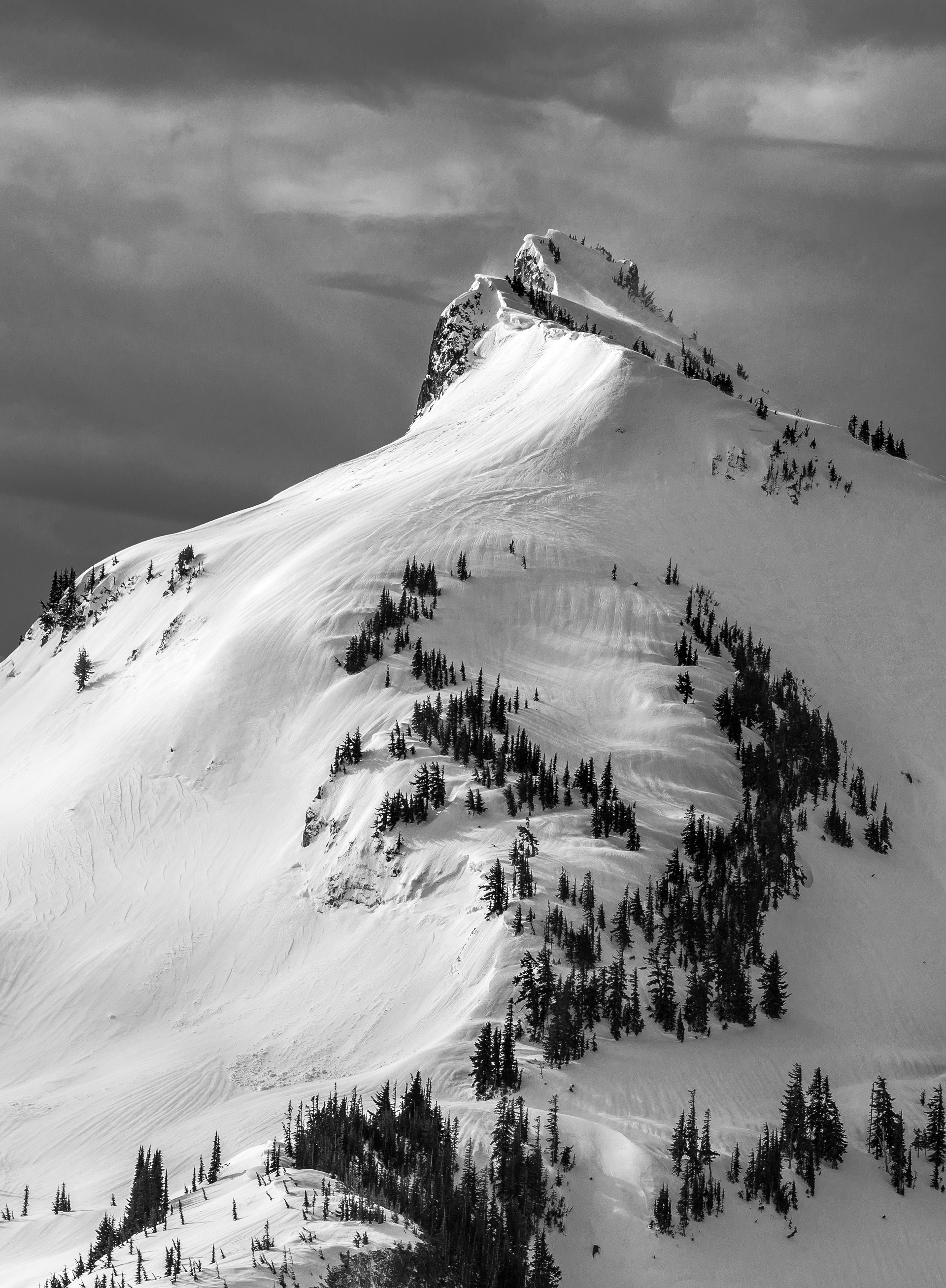 High winds blow snow up over the top of Manatee Mountain in the Tatoosh Range, Mount Rainier National Park, WA