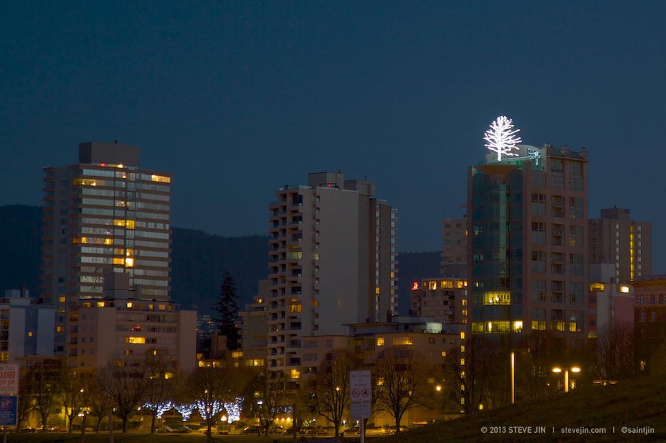 """The tree on top of this condo has been around for few decades now. I remember seeing for the first time and thinking, """"What the heck… where are the roots gonna go?!""""   I still don't know the answer. Anyone know?   Anyway when it's lit up like this it reminds me of the White Tree of Gondor from the Lord of the Rings books/movies. Just without the benevolent, healing king and the giant city of Gondor supporting it.   I may just call that building Gondor from now on.   - sj"""