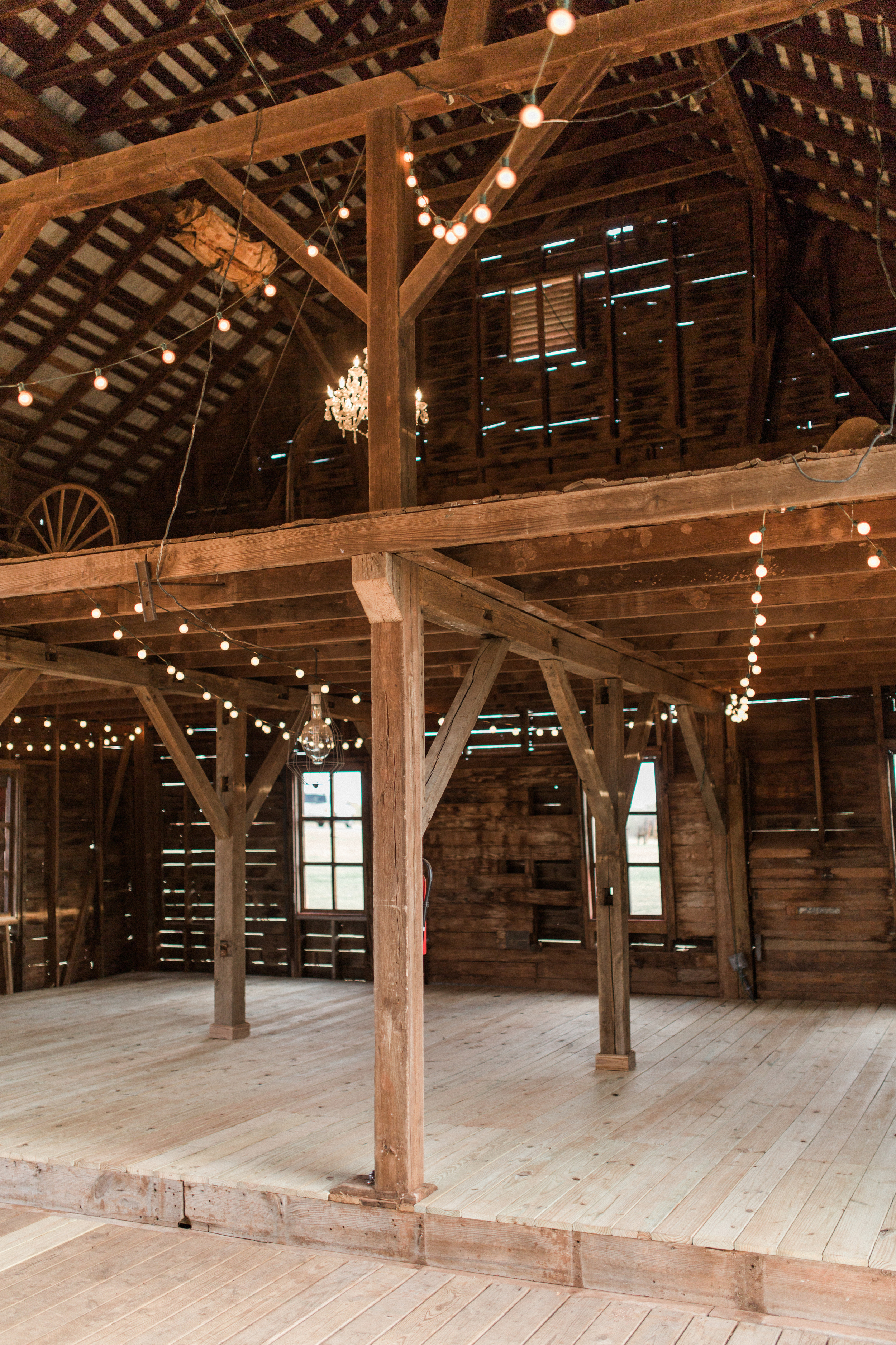 "With two of our rooms' walls knocked down, even more square feet have been added for your event! If you're familiar with the large chandelier in the middle of the barn, we installed a ""sister"" chandelier and even more bulb lights to make your event truly sparkle!"