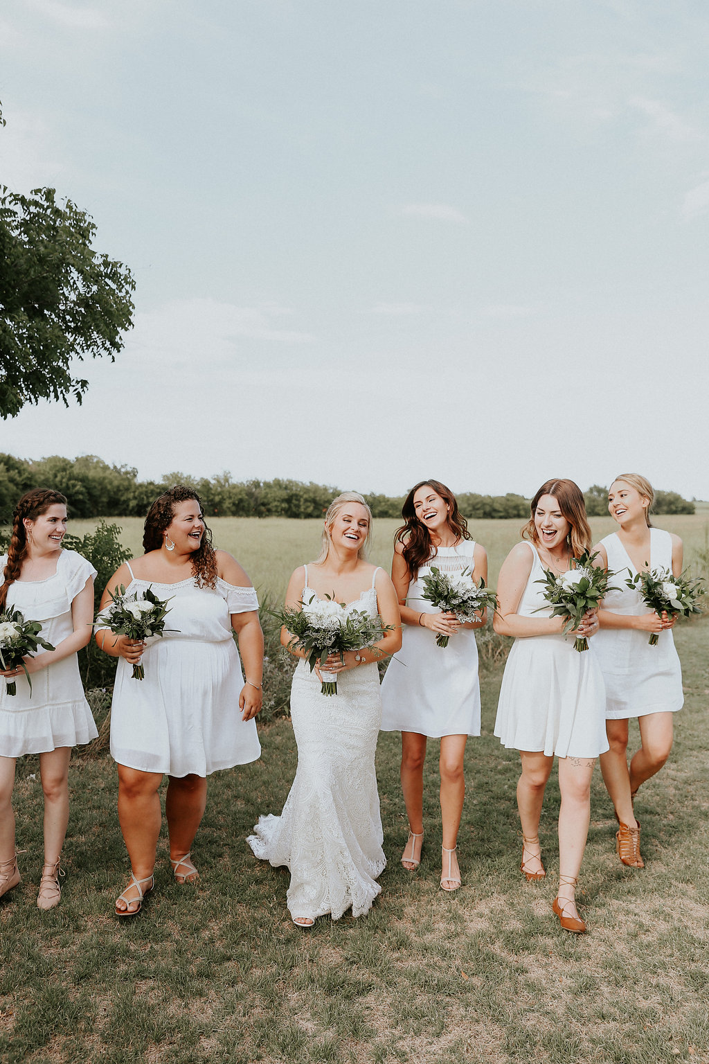 These mix-matched, white bridesmaid dresses gave the whole wedding party a fresh and simple look that is a beautiful trend this season, especially when paired with the extra greenery in the bouquets!