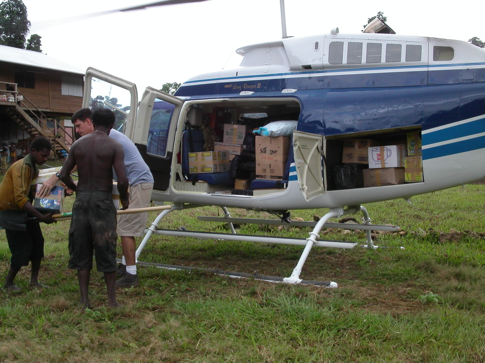 Helicopter with internal cargo load, village, Papua New Guinea (PNG)