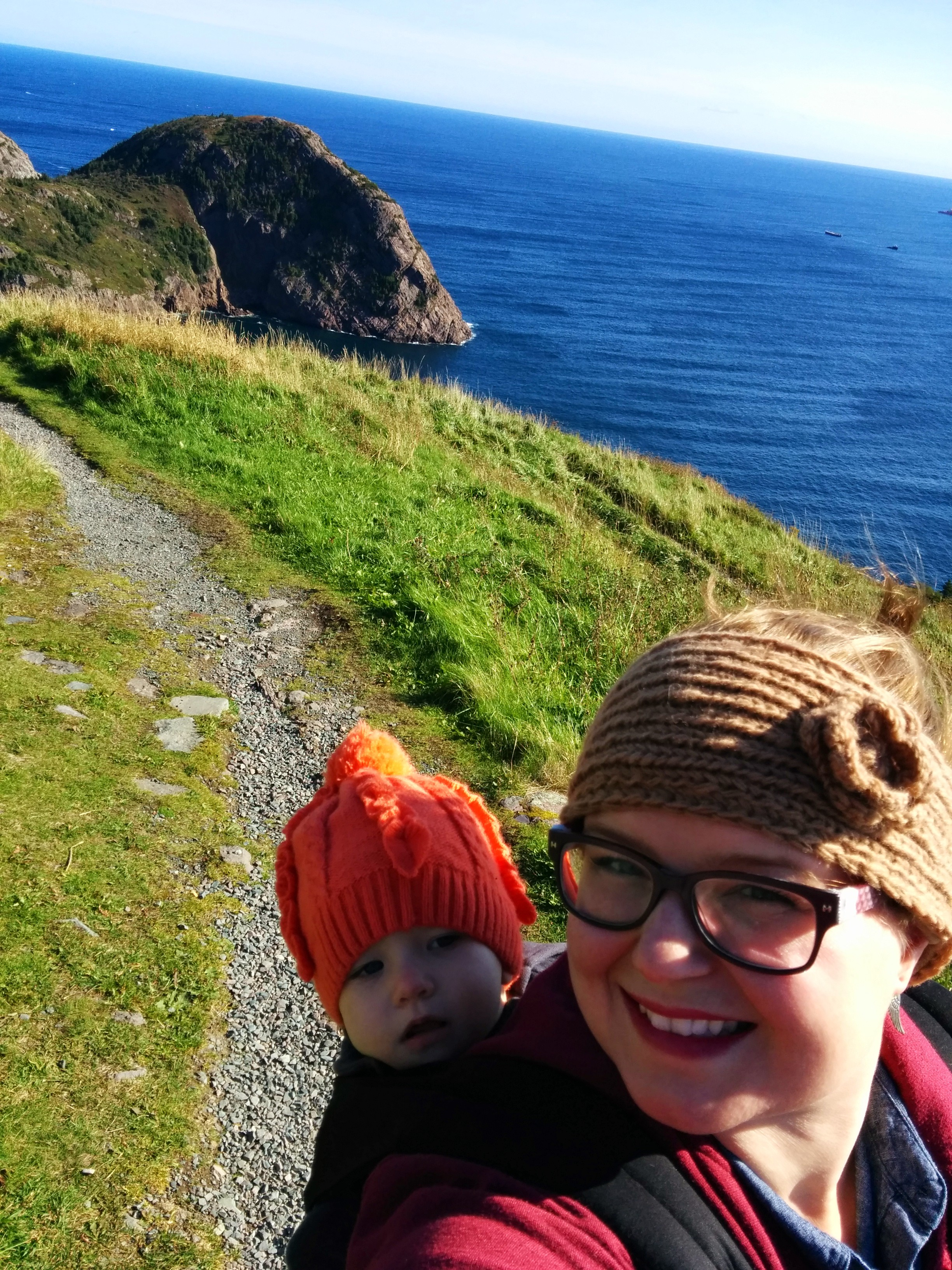 On Signal Hill in St. John's, Newfoundland. [Image description: a white woman with large purple glasses takes a selfie. She is wearing a brown headband and a child on her back, who is wearing a bright orange tuque. They are standing on a rocky and grassy trail in front of a big blue ocean behind them.]