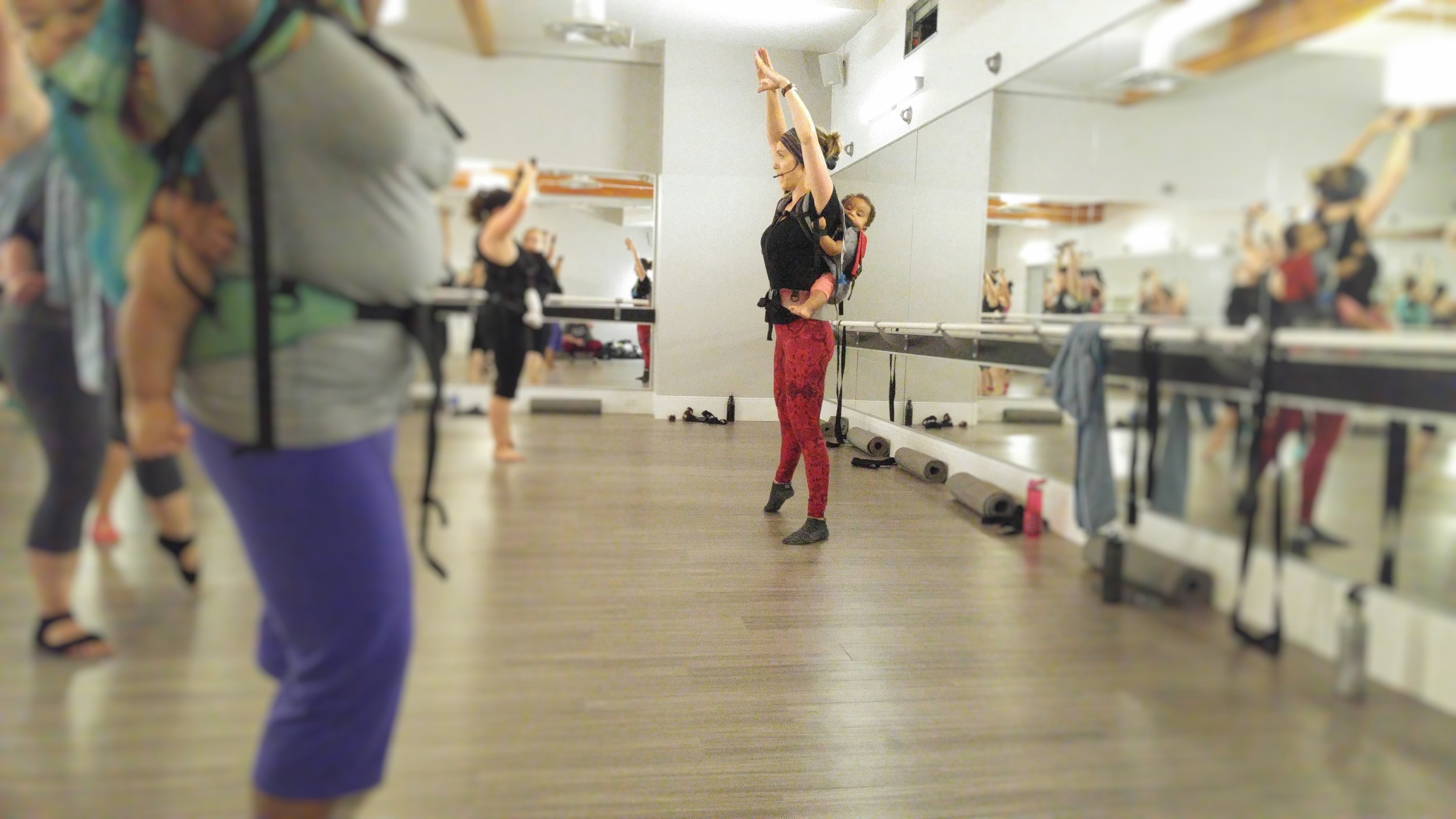 Bethany wearing her son while teaching a barre class at Xtend Barre Edmonton. [Image description: A woman stands in the centre of a mirrored room teaching a barre class. She is wearing red pants and wearing a child on her back. The rest of the room is blurred and shows other mothers participating in the class as well as mirrors reflecting that scene.]