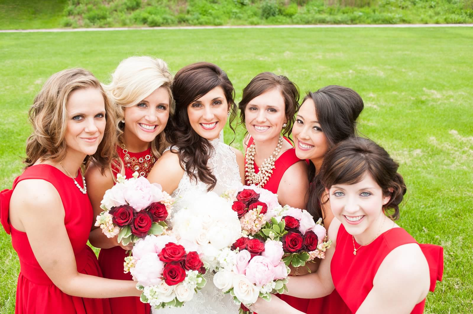 Bride and bridesmaids with red, white, and pink bouquets.jpg