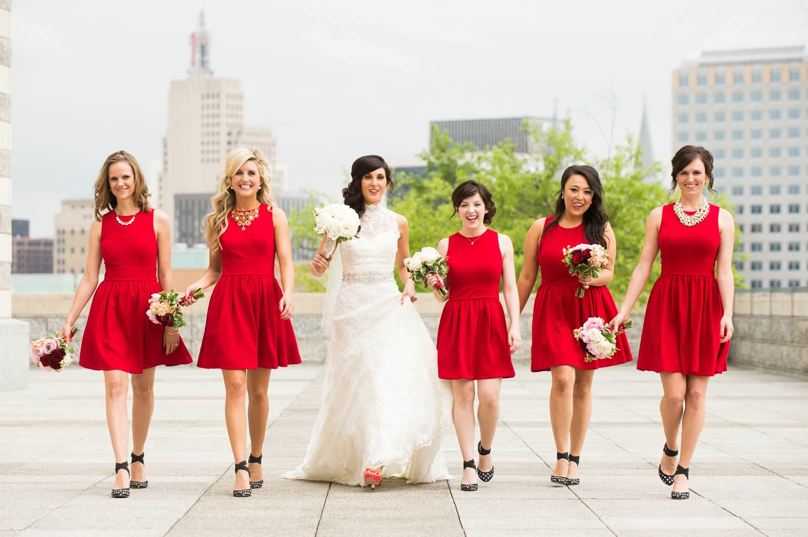 Bride and bridesmaids walking with red bridesmaid dresses and red, white, and pink bouquets.jpg