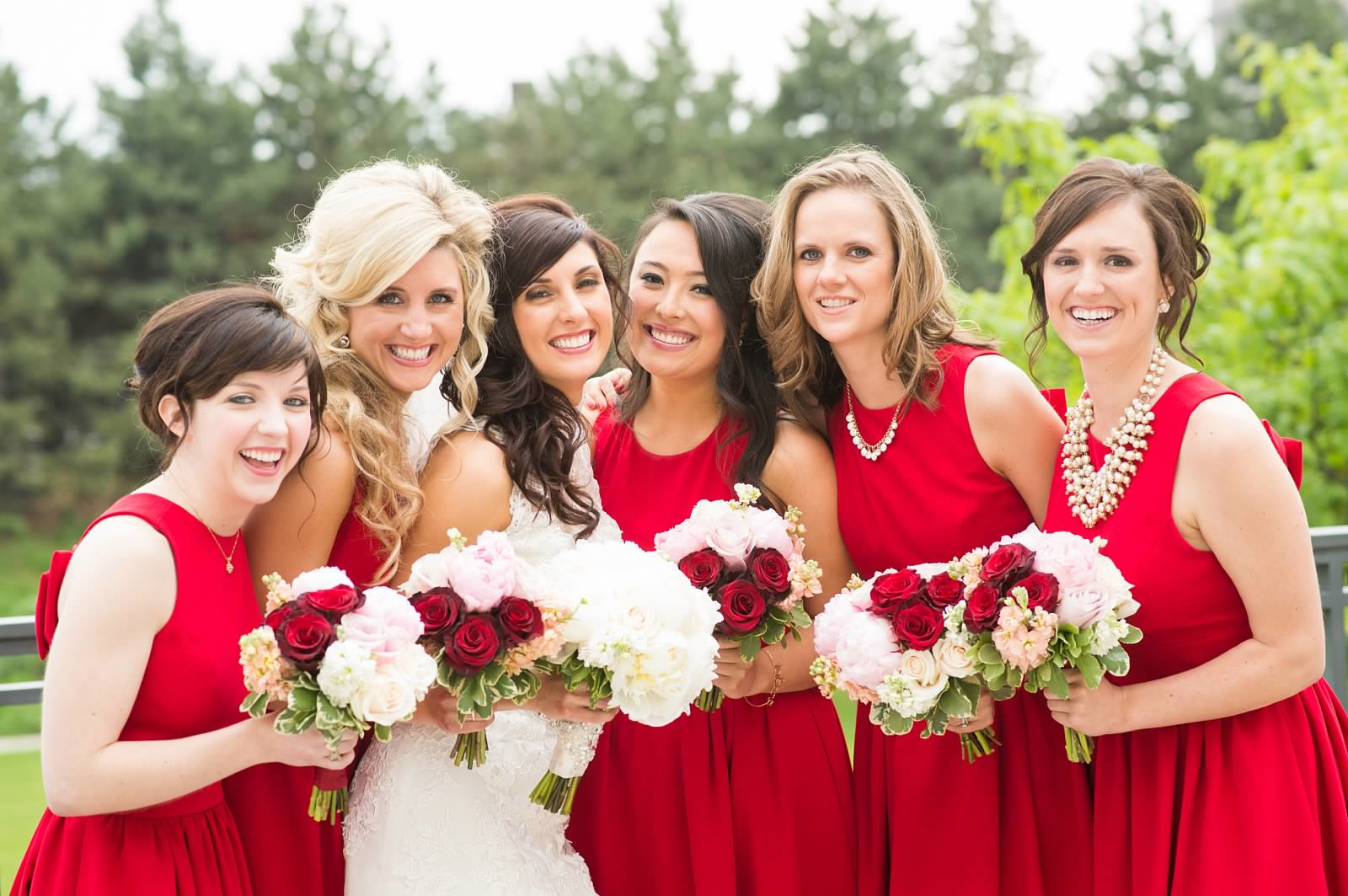 Bride and bridesmaids with red, white, and pink bouquets 2.jpg
