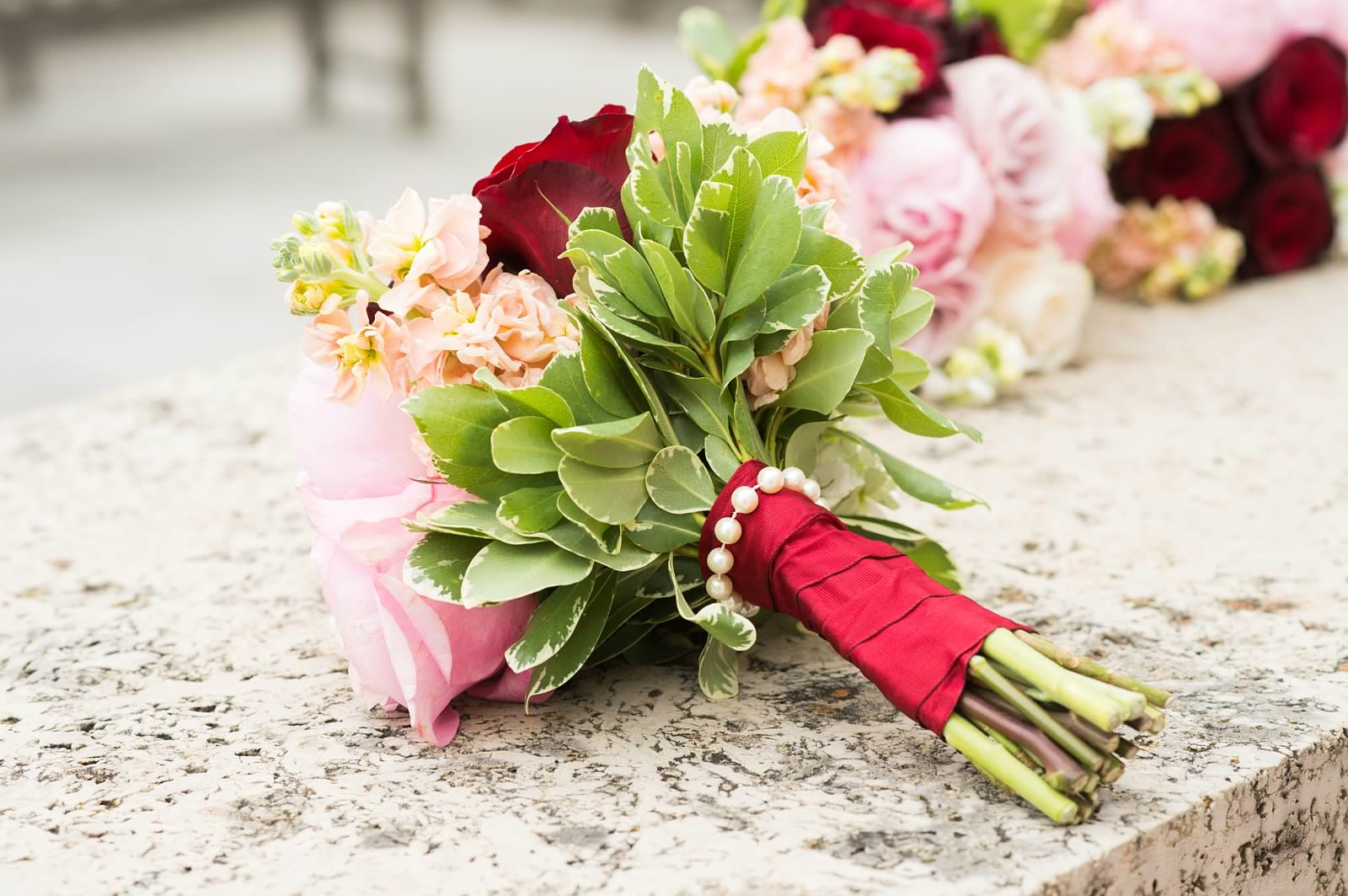 Bridesmaid bouquet with red Paris roses, pink roses, and coral stock wrapped with raspberry red French wired silk ribbon with a pearl collar.jpg