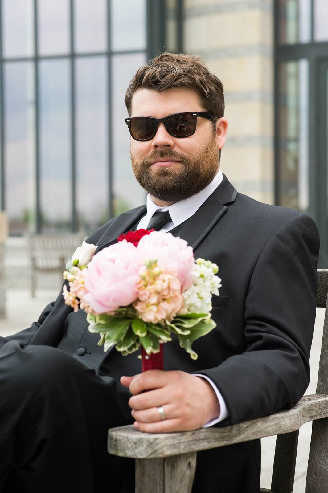 Dapper groomsman in sunglasses holding red, white, and pink bridal bouquet.jpg