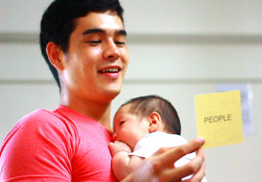 Alex draws a people card and reads it to the group while holding his infant son who arrived during game development :)