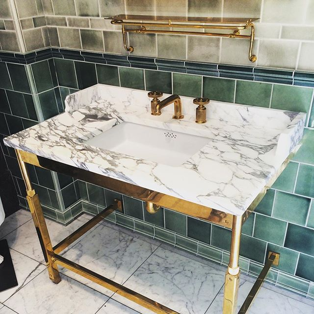 Very chick and elegant with a mix of tiles, marble and brass.