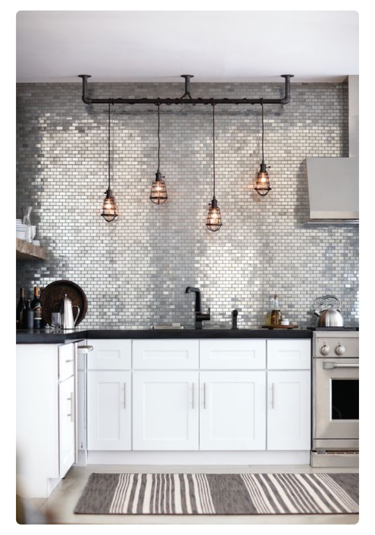 Silver mirror-like ceramic tiles make a simple kitchen wall like this much more interesting.