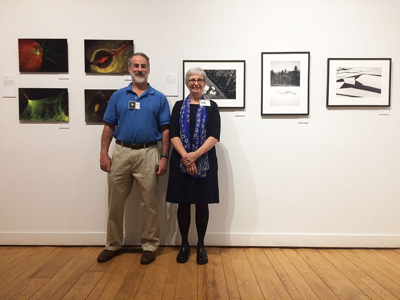 Charlie Mazel and Diane Bennett with their images at the Atelier exhibit opening.