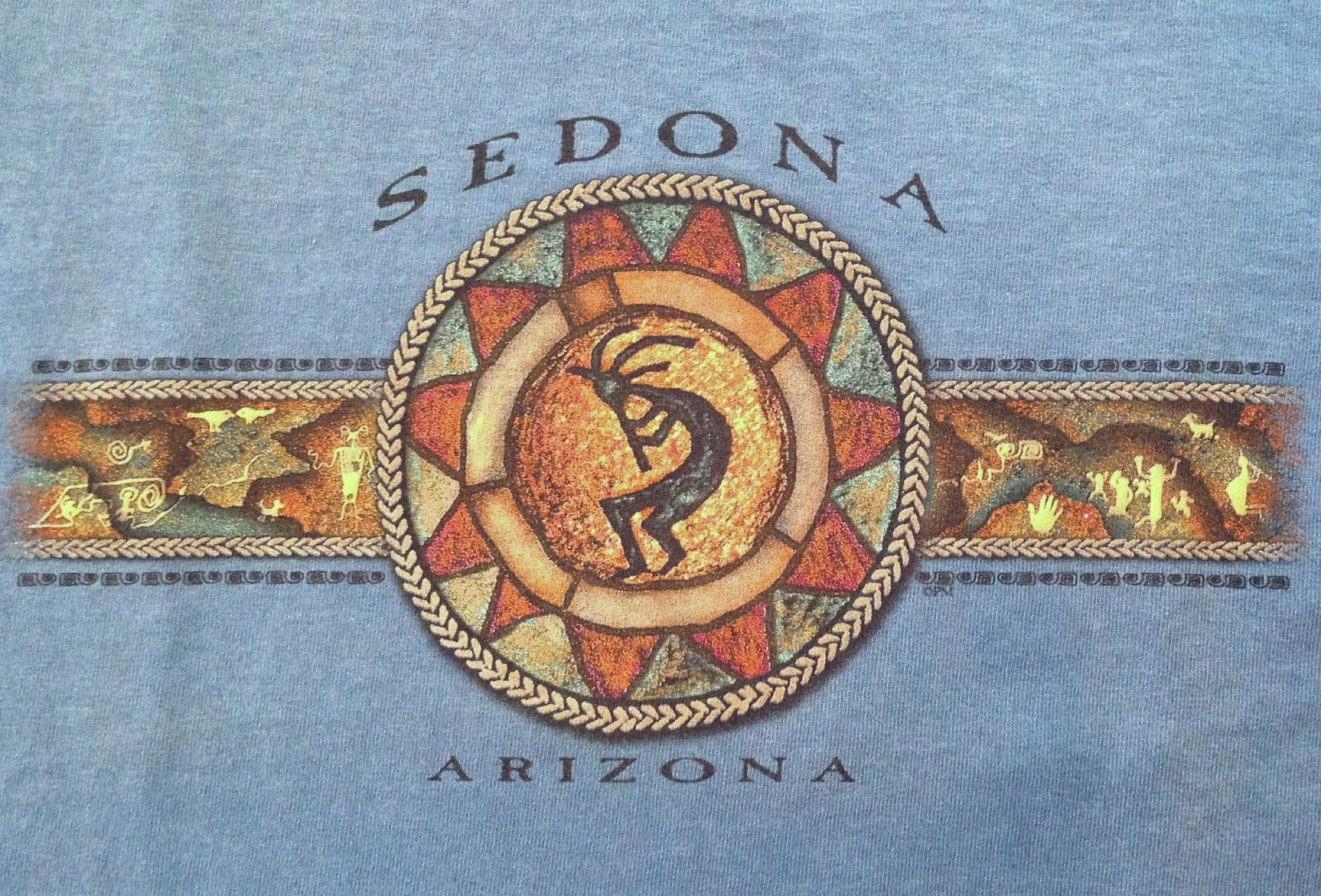 Kokopelli is a Native American petroglyph design found in Sedona and Arizona. Cotton t-shirt available in Rust and Blue.