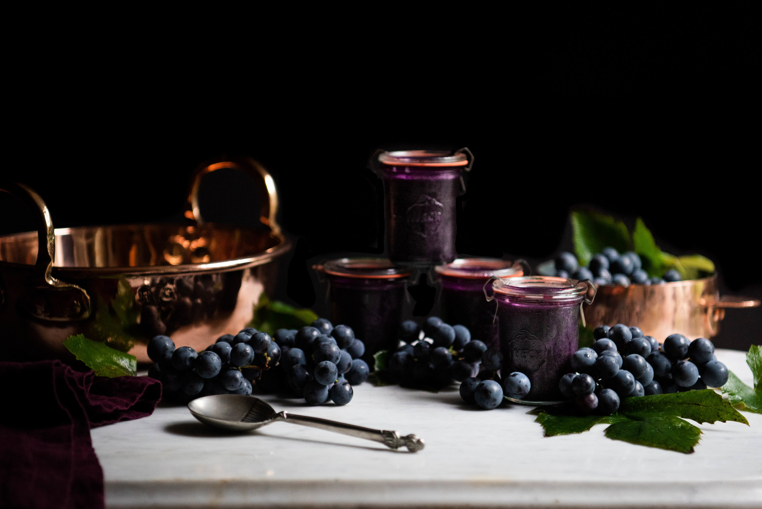 Concord Grape Jelly - This is a grown up grape jelly—not cloyingly sweet, gem toned, mildly tart, and the texture of velvet on the tongue. It is one of the simplest recipes in the world, yet complex it its depth of flavor. Intensely aromatic, the Concord grape dates back to the mid 19th century where among his neighbors Ralph Waldo Emerson, Henry David Thoreau, Nathaniel Hawthorn, and the Alcott family, a farmer began experimenting with grape seeds from some native species in search of the perfect grape. This horticulture endeavor lead Ephraim Wales Bull to plant more than 22,000 seedlings before he was satisfied that he had cultivated a full-bodied grape that would thrive in rugged New England soil, ripen early, and survive the frosts that killed European cuttings. While Mr. Bull developed the standard for grape taste, it is the dentist, Mr. Welch, that commercialized and profited from this native vine. He sold most of his first presses of the grape to churches to use during the sacrament, but soon decided to employ Louis Pasteur's pasteurization methods to stop fermentation and deliver a safe, mass marketed non-alcoholic juice to the market.Wildly popular, Mr Welch continued with his kitchen science experiments and in 1918 produced World War I jam rations for American soldiers. It was, however, during World War II that one of the classic and most beloved of all childhood lunches came to be—the PB&J was invented as a means of providing troops with more nutrition in the form of inexpensive nut protein. Dr. Welch's Concord jam became the standard by which all peanut butter and jelly combinations are measured even today. Try this less sweet, no additive homemade jelly on baked brie, grilled cheese made with cheddar or fontina, pork and duck plates, PB & J's, or vanilla ice cream. Only in season for a few weeks each fall, relish the opportunity to make your own preserves. Do preserve enough of this quintessential New England autumn harvest with friends and family.