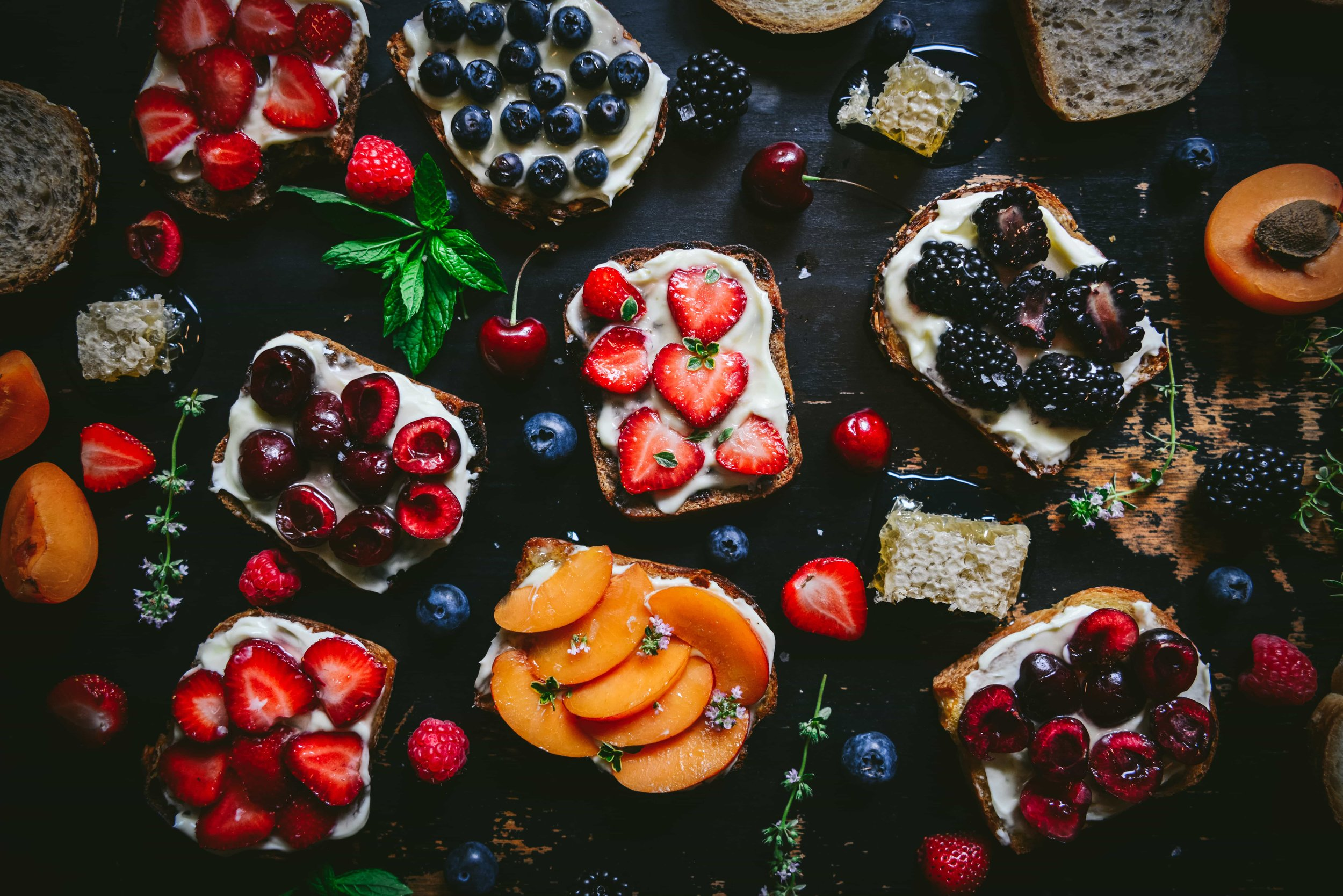 Summer Fruit Mascarpone Toasts - When the strawberries are ripe, it is a sure sign that summer has arrived in New England. These juicy, heart-shaped, scarlet garden berries are genetically related to the garden rose and are best when fresh from the field. Blackberries and blueberries seem to be the best of year-round available fruit and are easy to find organically grown. California grows delightful late spring apricots and the first North-American cherries that hit the market just as strawberries are at their summer solstice best. For a particularly delightful Sunday brunch, toast slices of rye, brioche, country, and raisin pecan bread from a favorite bakery, slather with mascarpone cheese, drizzle with local honey, sprinkle with sea salt flakes, and dot with tiny mint sprigs or lemon thyme. Rustically elegant, this fruit and bread cornucopia pairs perfectly with bubbly. There must be something to celebrate….go ahead and pop the cork!