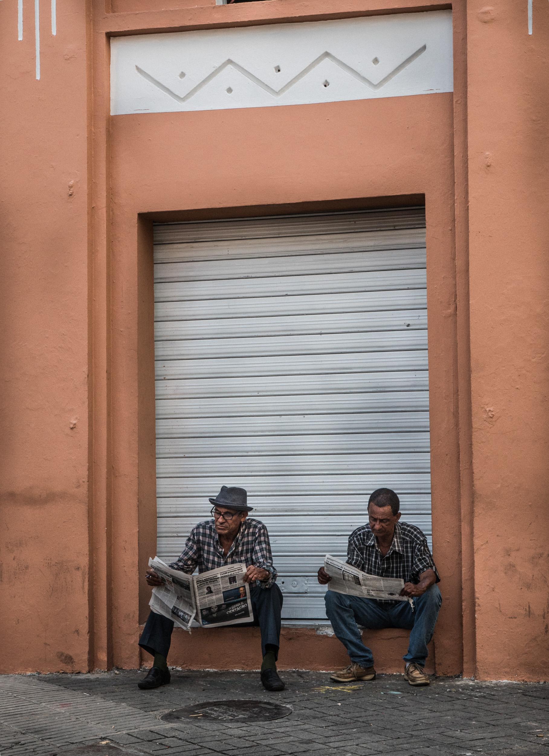 _37 Two Men Reading newspaper orange wall Santo Domingo.jpg