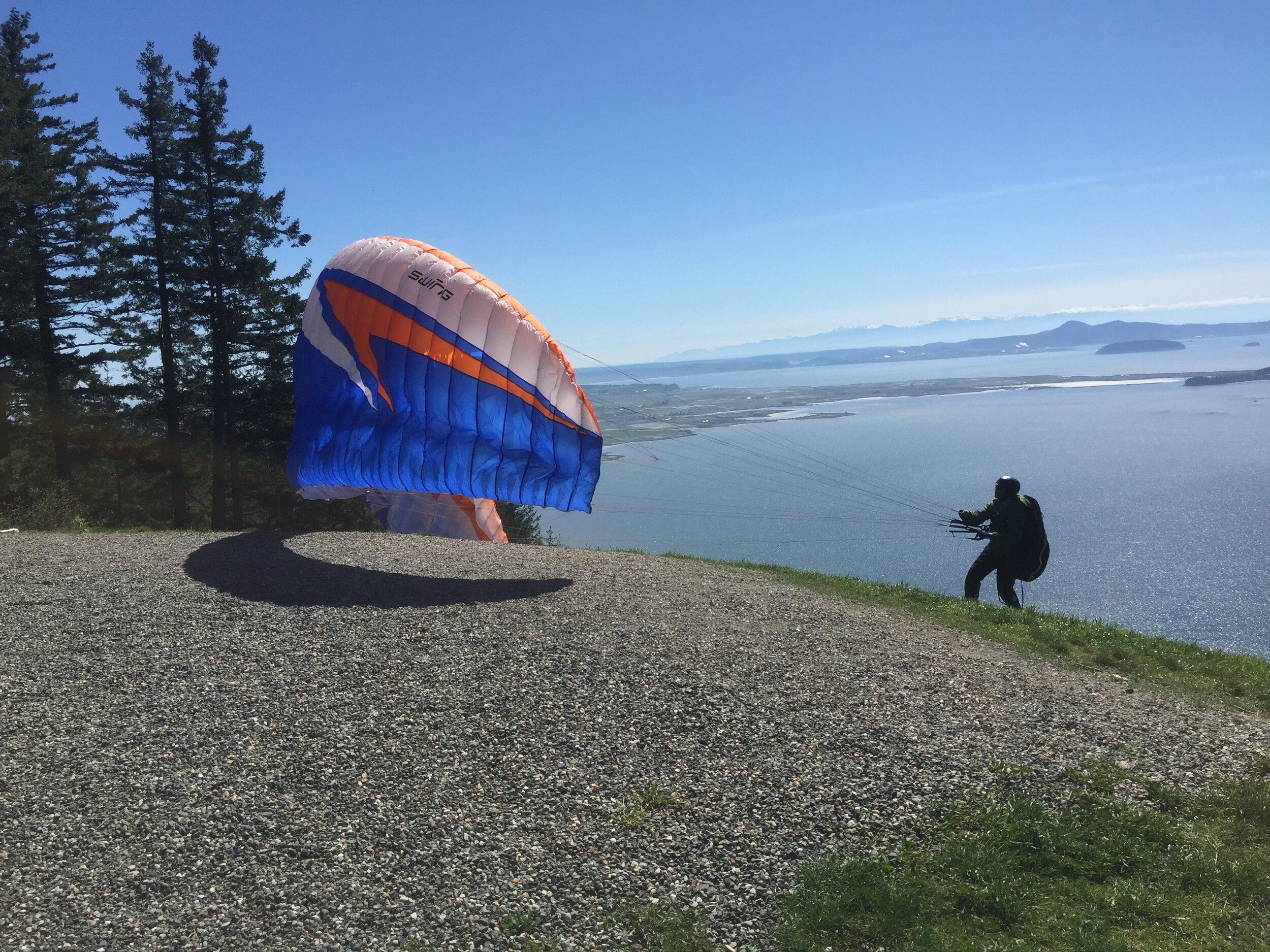 A paraglider about to launch from Samish Overlook.  The paraglider has learned through many previous acts of trust to do this with confidence.   Will we entrust ourselves to the newness and promise of God in this moment? -Photo by author