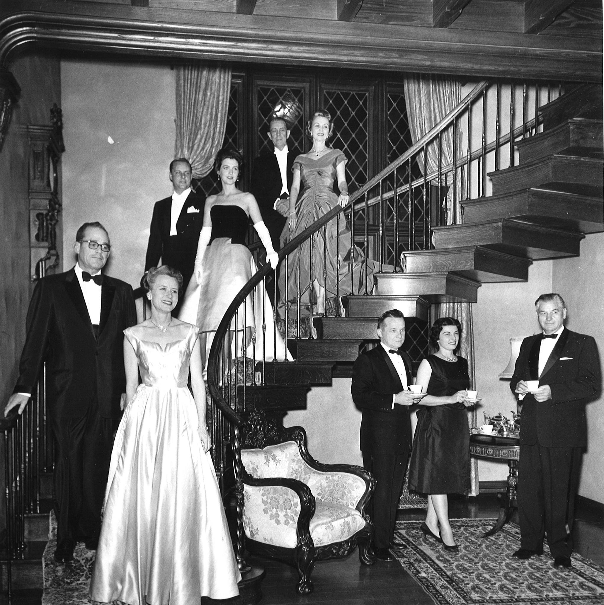 Sybil Harrington at one of her balls (Pictured in Green Dior dress, highest on staircase)
