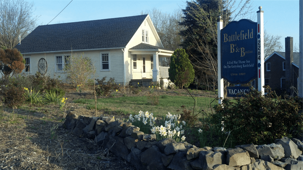 Roadside view of Battlefield Bed and Breakfast Inn's sign and the cottage