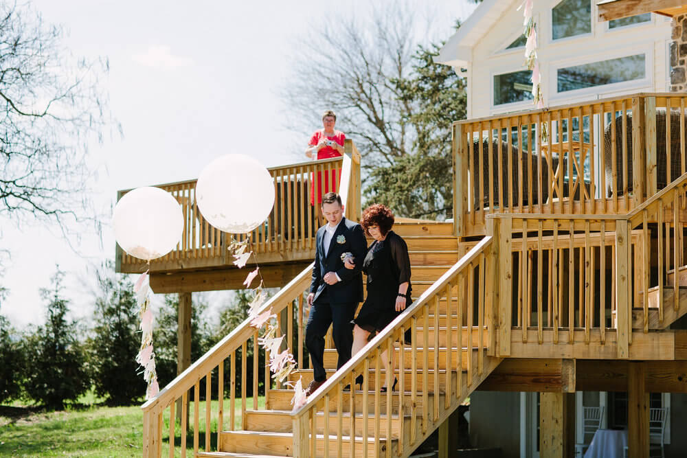 Copy of wedding party walking down the deck stairs to the wedding garden below