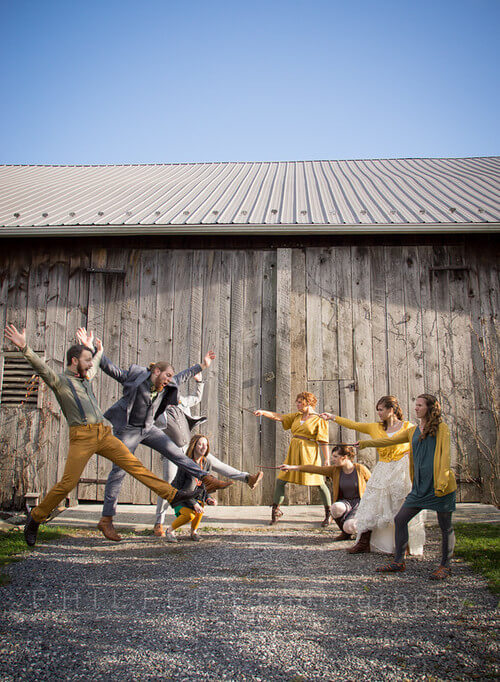 Copy of wedding party in an action shot in front of the historic barn event venue