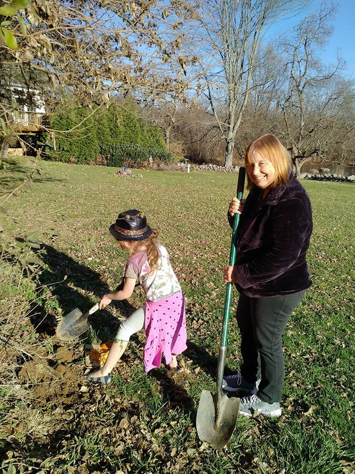 Florence planting pumpkin seeds in the vegetable garden with her granddaughter Alice.
